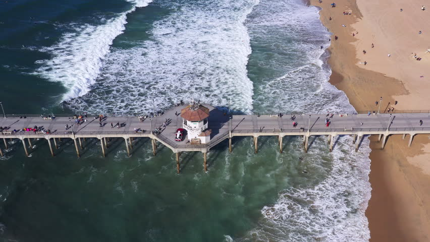 Drone aerial of lifeguard headquarters tower on pier with tourists   Shutterstock HD Video #1023976031