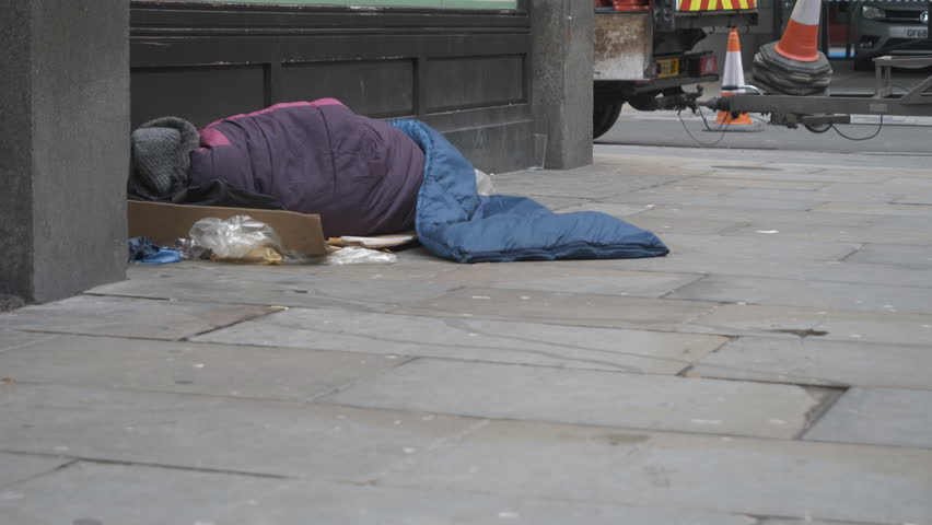 A homeless man sleeping on the street.