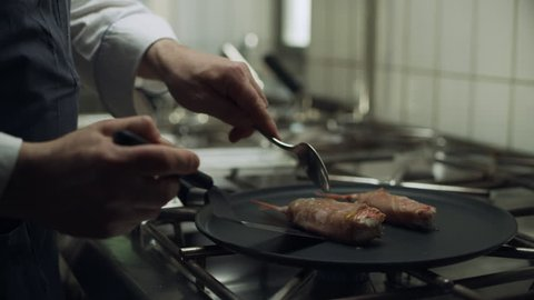 Professional restaurant chef cooking large shrimp wrapped in bacon on a skillet over a burner to cook. Close up shot on 8k helium RED camera.