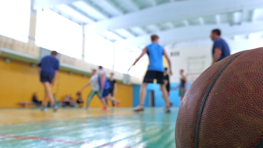 Basketball game. Teens train in the school old sports hall, throw the ball in the basket and run with the ball. | Shutterstock HD Video #1024080461