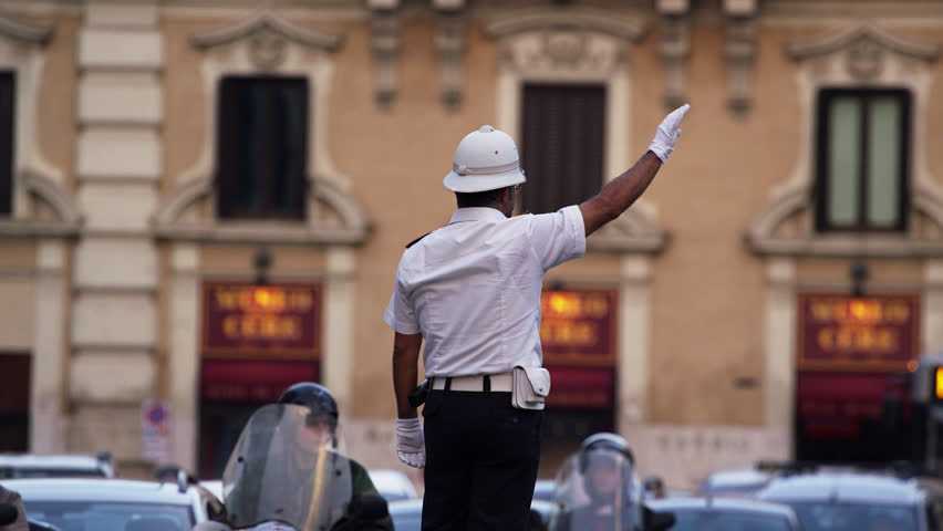 A traffic officer directs traffic in Rome, Italy