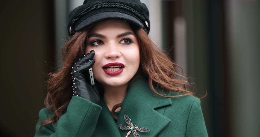 Stylish woman in green coat and beret talking on phone in the street. | Shutterstock HD Video #1024110071