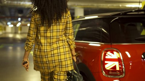 Businesswoman with curly hair, getting on the driver seat of a red mini cooper car at the parking lot (medium shot)