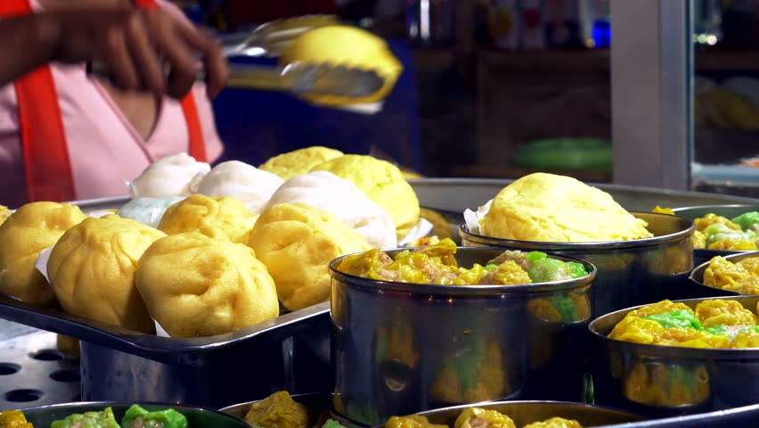 Traditional street food of Thailand. Cooking national dishes at night in the street food market. close-up. cooking Baozi Steam Pies close-up.   Shutterstock HD Video #1024128041