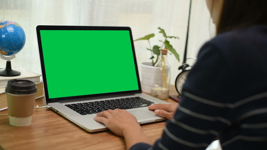 Over the shoulder shot of a woman typing on a computer laptop with a key-green screen in home office. | Shutterstock HD Video #1024130681