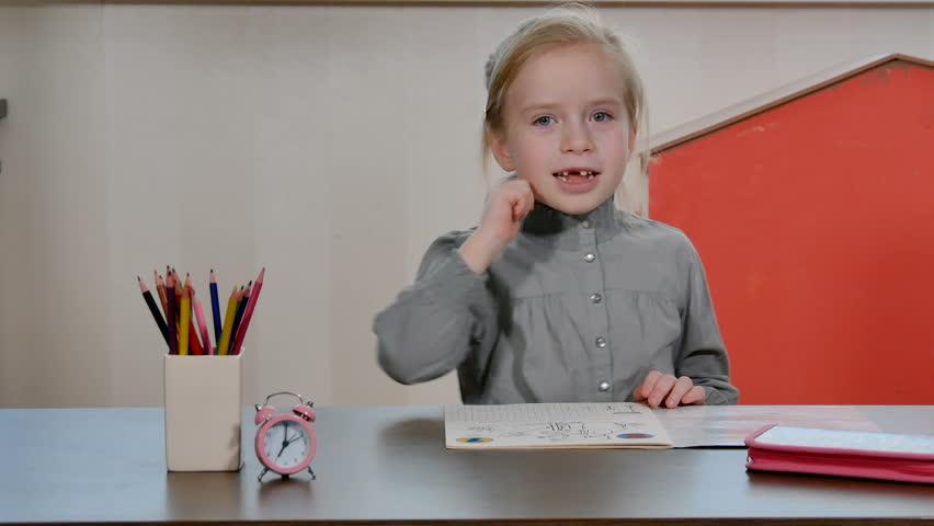 Tired and bored little preschool girl sleep on homework desk. Pretty female pupil do homework and school exercises. Home education concept | Shutterstock HD Video #1024162901