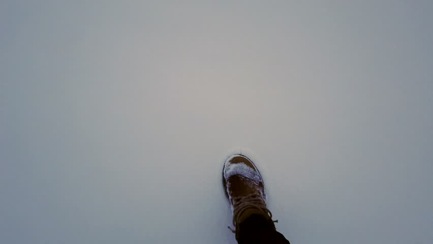 First-person view, person in yellow shoes leaves two footprints in the snow and turns away | Shutterstock HD Video #1024197791