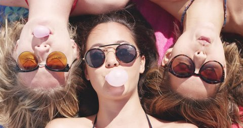 Top view of three teenage girl friends lying on back blowing bubblegum candy bubbles on beach