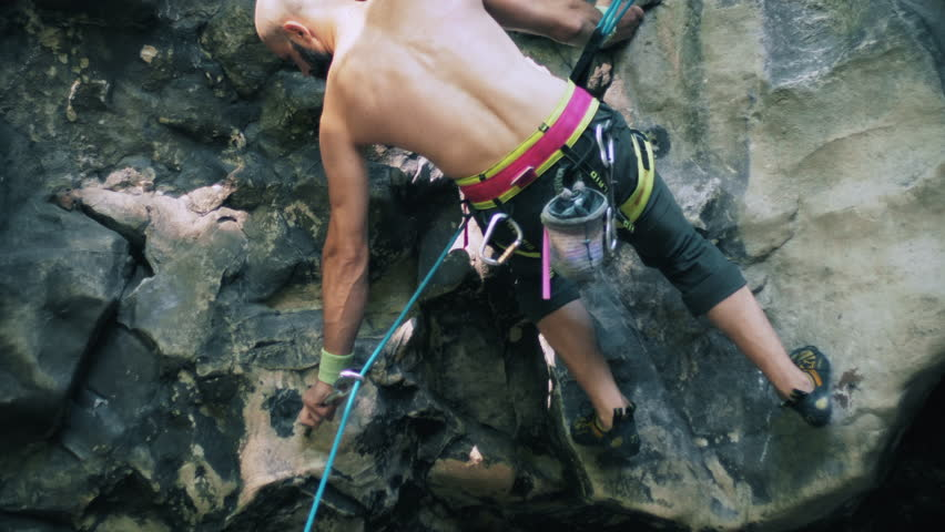Bearded mountain climber man descends down the rock on the insurance. Extreme outdoor sport activity climb cliff. Dynamic close-up shot filmed in 4k UHD 2160p | Shutterstock HD Video #1024237541
