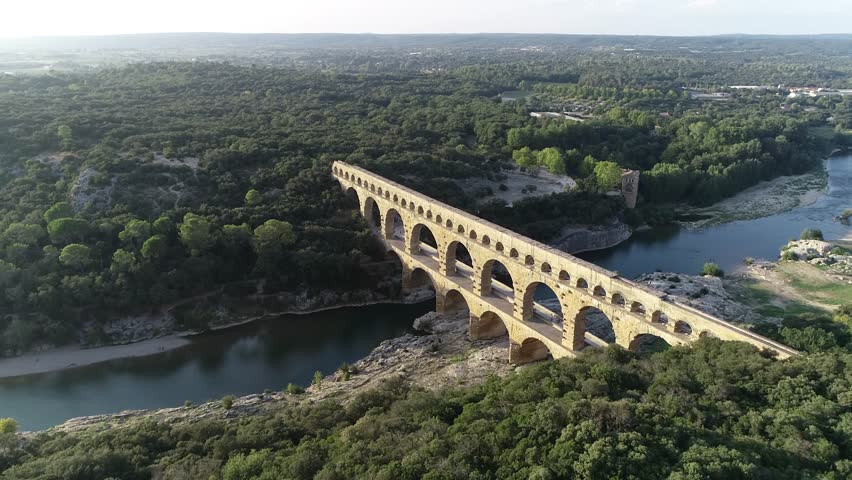 Aerial bird view footage Pont du Gard is ancient Roman aqueduct that crosses Gardon River near towns of Remoulins Avignon and Nimes in southern France it is on UNESCO's list of World Heritage Sites 4k | Shutterstock HD Video #1024272791