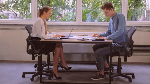 business team discussing project sitting at the desk near big windows in old office. caucasian man and woman working with documents at work