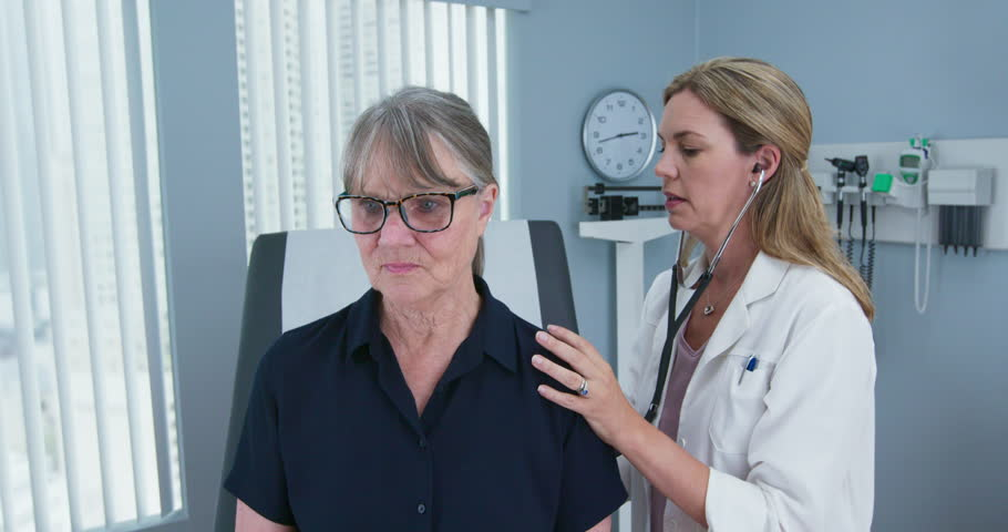 Female doctor using stethoscope listening to senior patients lungs. Older woman visiting her primary care physician for a regular check up. Slow motion 4k | Shutterstock HD Video #1024302431