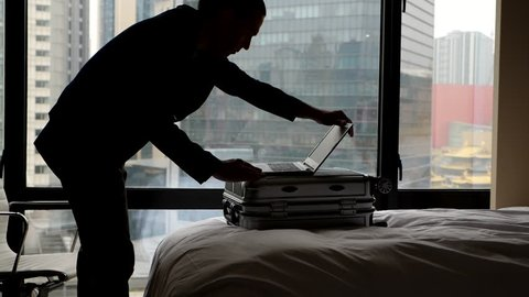 Man enter hotel room, put suitcase on bed and laptop on it, stoop over and turn on notebook. Super slow motion shot, dim interior, office buildings seen outdoors