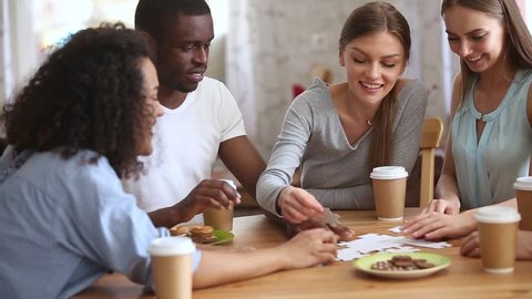 Diverse friends group assembling puzzle on table having fun drink coffee together, multiracial young people students talking laughing playing board game, international friendship leisure activities