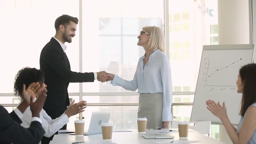 Proud male boss welcoming new female partner at group meeting handshaking congratulating with promotion get team applause, appreciating for good work, supporting recognition respect rewarding concept