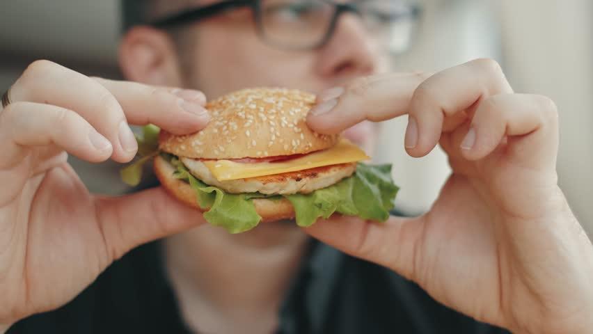 Man eating a hamburger. close-up shot. Fast food eats   Shutterstock HD Video #1024307261