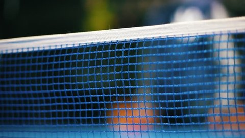 Closeup of net on blue table for ping-pong. Blurred person playing table tennis.