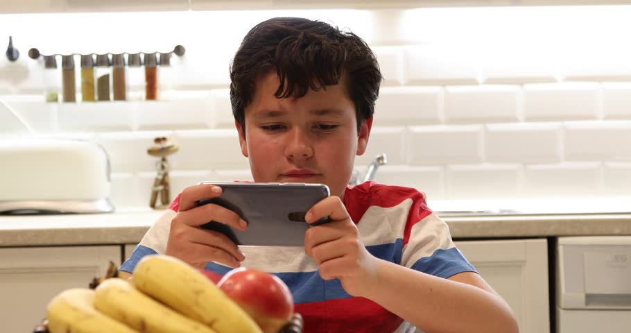Portrait of a preteen boy with smartphone sitting in the kitchen Kid watching to screen, reading, typing, playing games | Shutterstock HD Video #1024340321