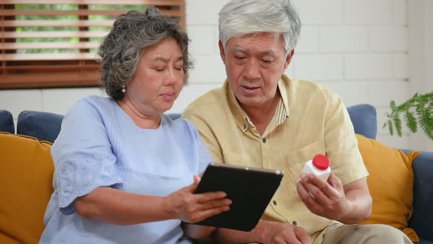 Asian senior couple searching for having medical consultation on tablet. Sharing social media communication and sitting on sofa at home. Slow motion | Shutterstock HD Video #1024349921