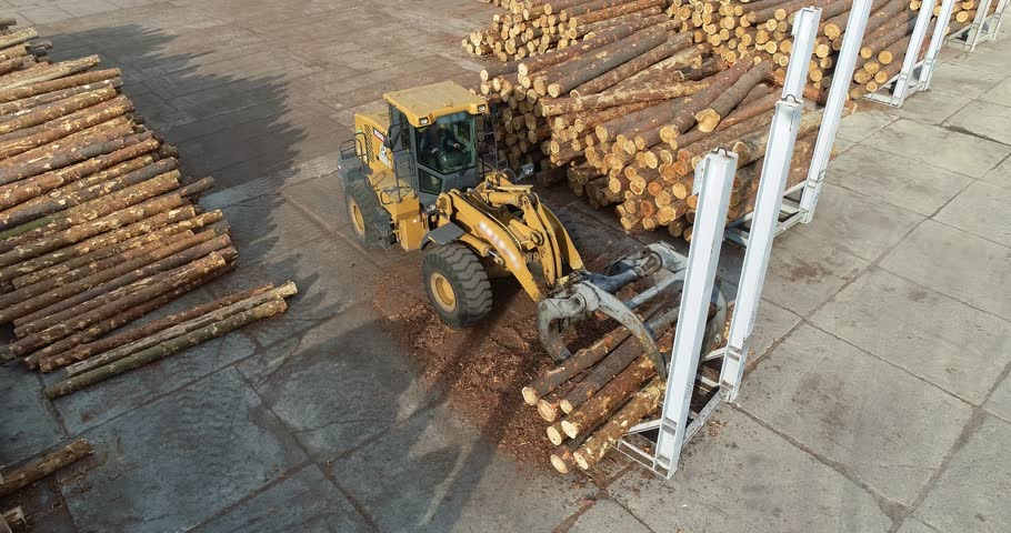 Yellow bulldozer transports logs at the sawmill, heavy machinery, workflow in the factory top view | Shutterstock HD Video #1024379021