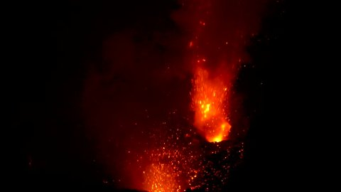 CLOSE UP: Stunning shot of Mount Yasur erupting at night and belching out glowing red magma. Dangerous molten lava and flames explode in the air during a violent volcanic eruption in Tanna, Vanuatu.