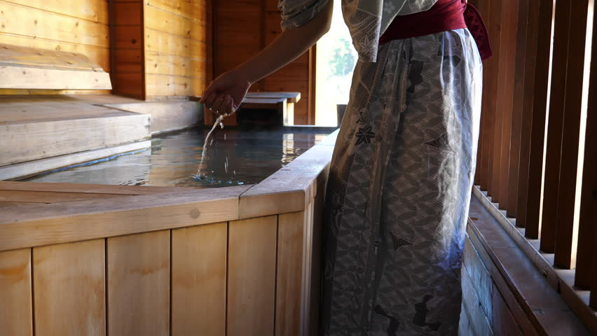 Woman wearing yukata head the water temperature before taking a relaxing bath | Shutterstock HD Video #1024395101