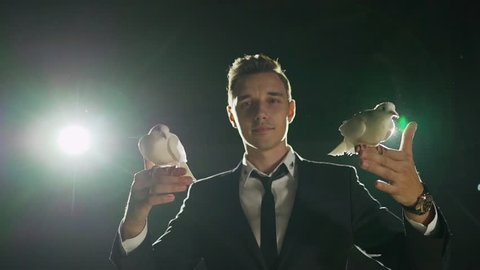 Male magician with white pigeon on dark background