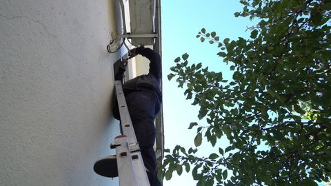 Air Conditioning Repair Young repairman on the ladder fixing air conditioning system Model is actual electrician