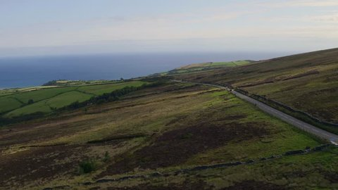 Aerial: Motorbike tracking shot on the Isle of Man TT course. Mountain section approaching Guthrie's Memorial. 4k