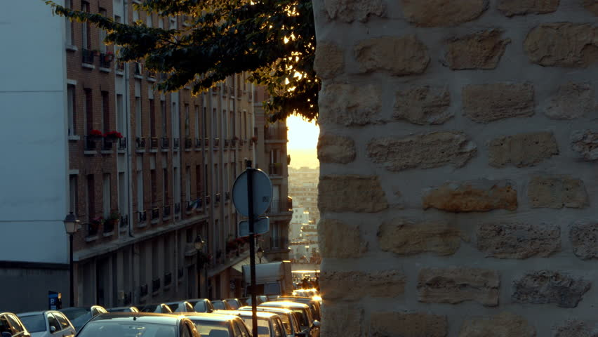 Sunrise in Montmartre a neighborhood of Paris, France. The sun is shinny orange to yellow through some leaf from a tree branches. Cars are quietly parked along the road.Becquerel street. | Shutterstock HD Video #10245083