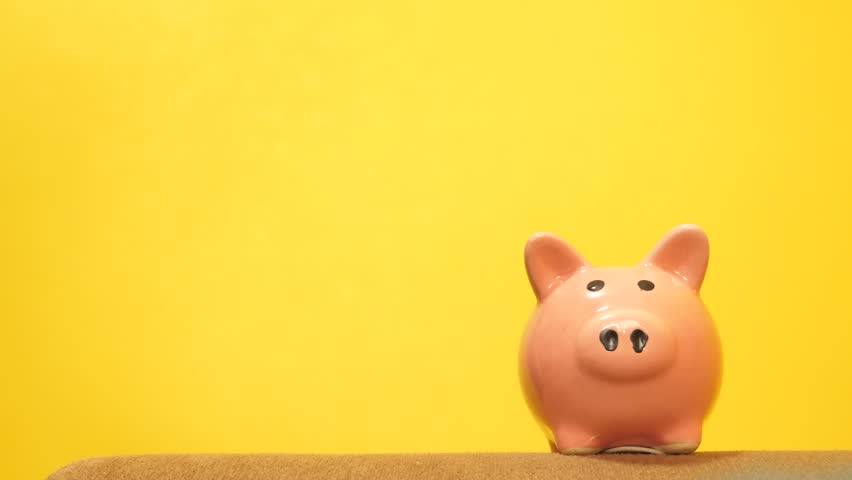 piggy bank lifestyle business concept. A hand is putting a coin in a piggy bank on a yellow background. saving money is an investment for the future. Banking investment and finance concept for your