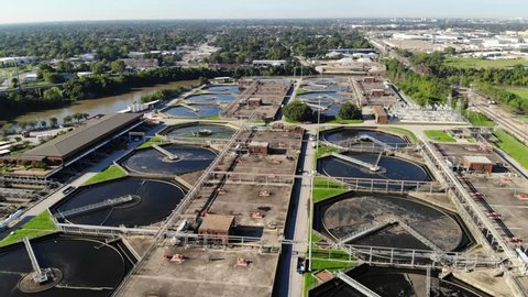 Aerial Drone Footage of a Sewage Treatment Plant next to Buffalo Bayou with the Houston Medical Center and the City of Houston Skyline in the Background