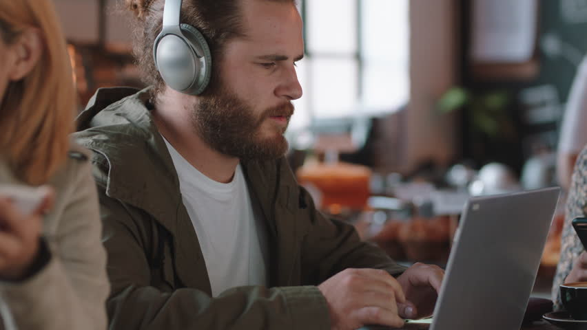 Young man using laptop in cafe browsing online listening to music wearing headphones enjoying mobile computer technology | Shutterstock HD Video #1024584041