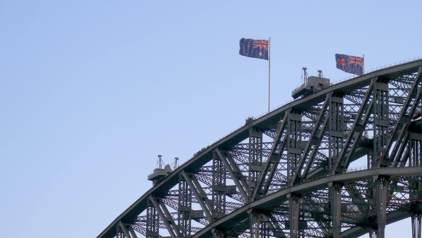 People walking on top of Sydney Harbour Bridge with two Australian flags waving in wind