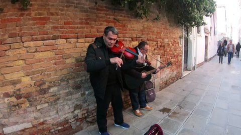 Venice, Italy / 03/02/2019 - Traditional folk music busking on street in Venice, Italy with guitars