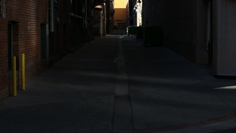 Tilt Up Reveal of Dark Dirty Alley Way with Brick Wall and Green Trash Dumpsters in Urban City - Shallow Depth of Field
