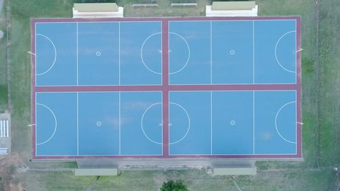 Slow aerial rise looking straight down at blue netball courts