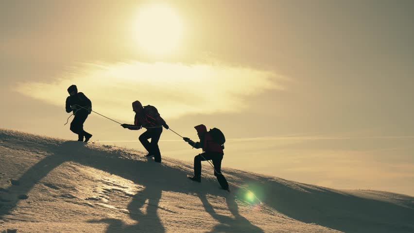 Tourists climbing a mountain snow cliff. Stretching a helping hand. People help each other. Teamwork, teamwork concept