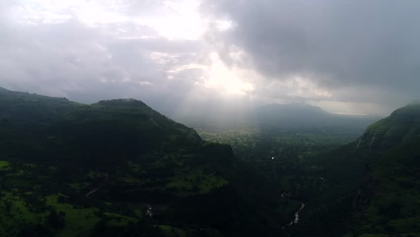 Aerial shot of early morning sun rays reaching the green surface of the mother earth passing through the clouds, surrounded by beautiful green mountains. | Shutterstock HD Video #1024669151