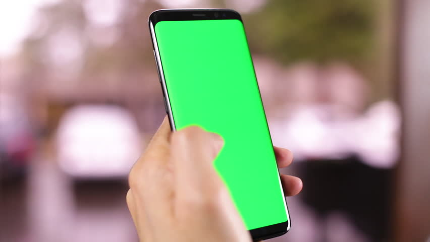 Women hands holding smart phone with green screen. Women using mobile phone while standing near window. Back view shot. Chroma key | Shutterstock HD Video #1024711481