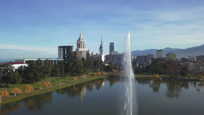 Aerial view of beautiful lake with the fountain in Batumi,Georgia.Green and yellow trees everywhere.Mountains and the sea in the background.A lot of modern buildings everywhere.Unfinished buildings. | Shutterstock HD Video #1024721891