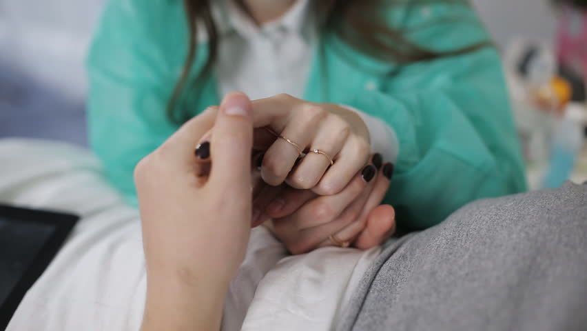 The patient lies in a bed in the hospital ward. The young girl holds carefully the hand of the patient | Shutterstock HD Video #1024767761