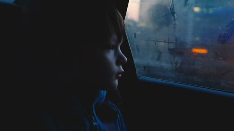 Atmospheric shot of little 4-6 year old thoughful Caucasian boy looking out of foggy car window in dusk dark evening.