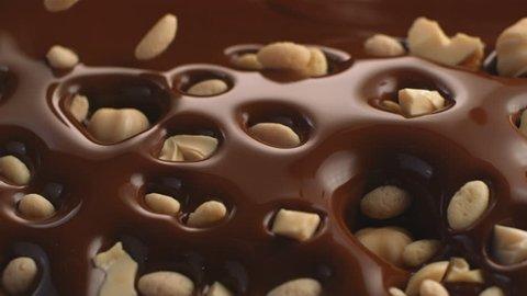 Rice Krispies hazelnut and hazelnut crack fall into chocolate bath waves in slow motion