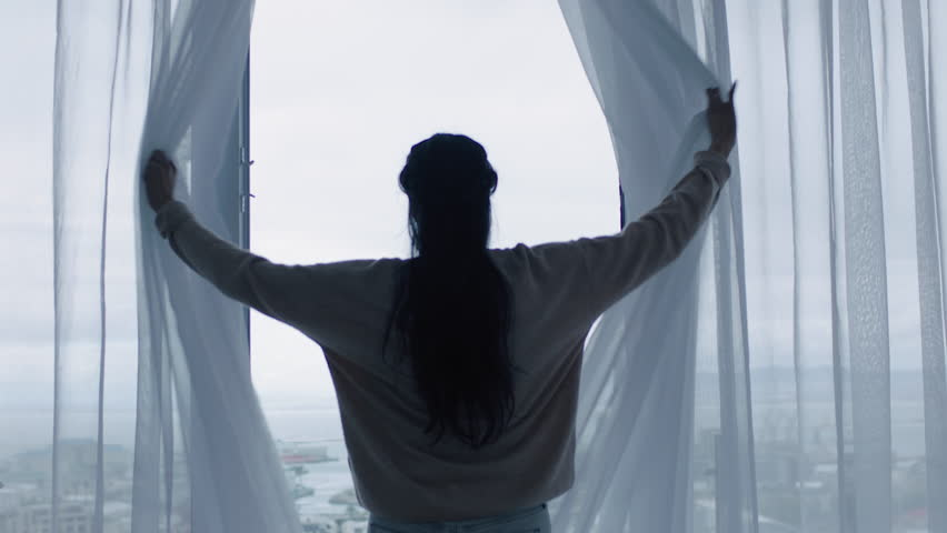 Happy young woman opening curtains looking out window ready for fresh new day feeling rested enjoying view of city | Shutterstock HD Video #1024807751