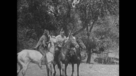 1920s: Indians with rifles ride on horseback. Man and woman talk on stagecoach. Indians mount horses and ride away from teepee.