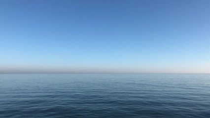 Video of calming waves of the North Sea/Ocean during a warm sunny morning with a blue cloudless sky at Roker Pier, Sunderland, Tyne and Wear, England UK.