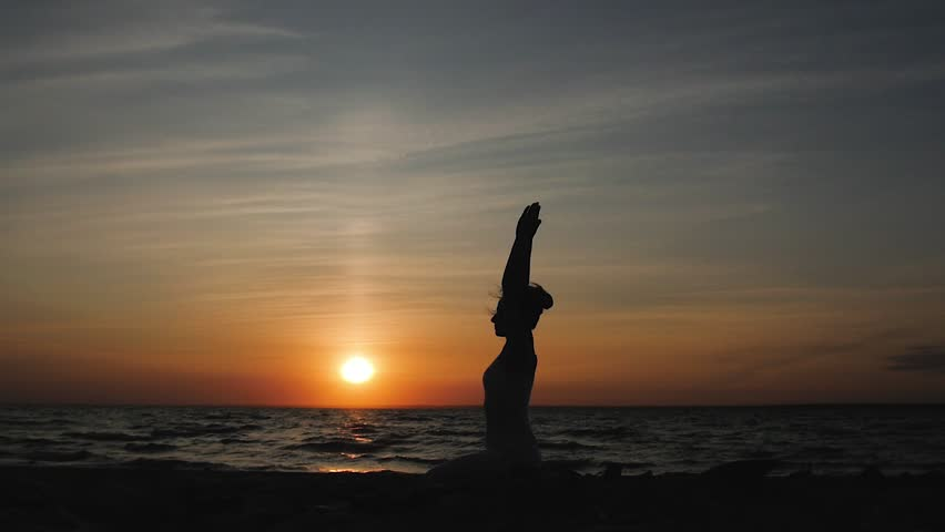 Woman doing yoga on the beach on the background of the water and the sunset, silhouette. kundalini yoga | Shutterstock HD Video #1024880381