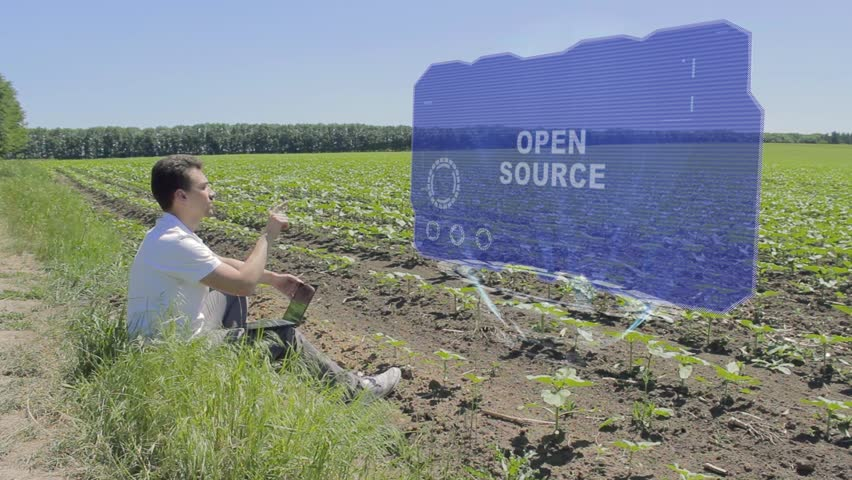 Man is working on HUD holographic display with text Open source on the edge of the field. Businessman analyzes the situation on his plantation. Scientist examines future technology | Shutterstock HD Video #1024939121