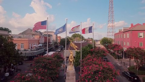 Aerial view of the gold Joan of Arc statue and flags of United States, France, New Orleans and Louisiana, in the late afternoon.